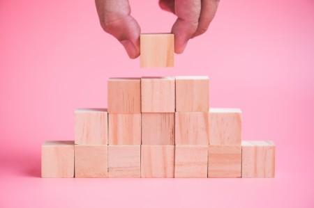 man-hand-building-stack-of-wood-cube-building-blocks_35570-712